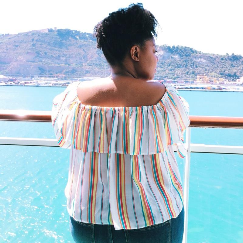 Black woman on balcony overlooking sea