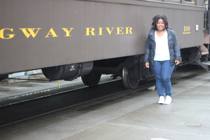 Black girl next to a train.